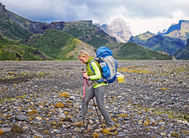 Woman hiker  with backpack walking up the trail stock photo
