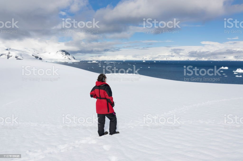 Woman hikes Antarctic Peninsula mountain overlook Orne Harbour Gerlache Strait Antarctica stock photo