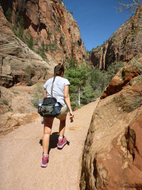 Woman hikes Zion National Park desert Angels Landing trail Utah canyon stock photo