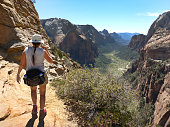 Overlooking the Great White Throne rock formation and Virgin River, a woman hikes along the red, desert Angels Landing trail in Zion Canyon in Zion National Park Utah.
