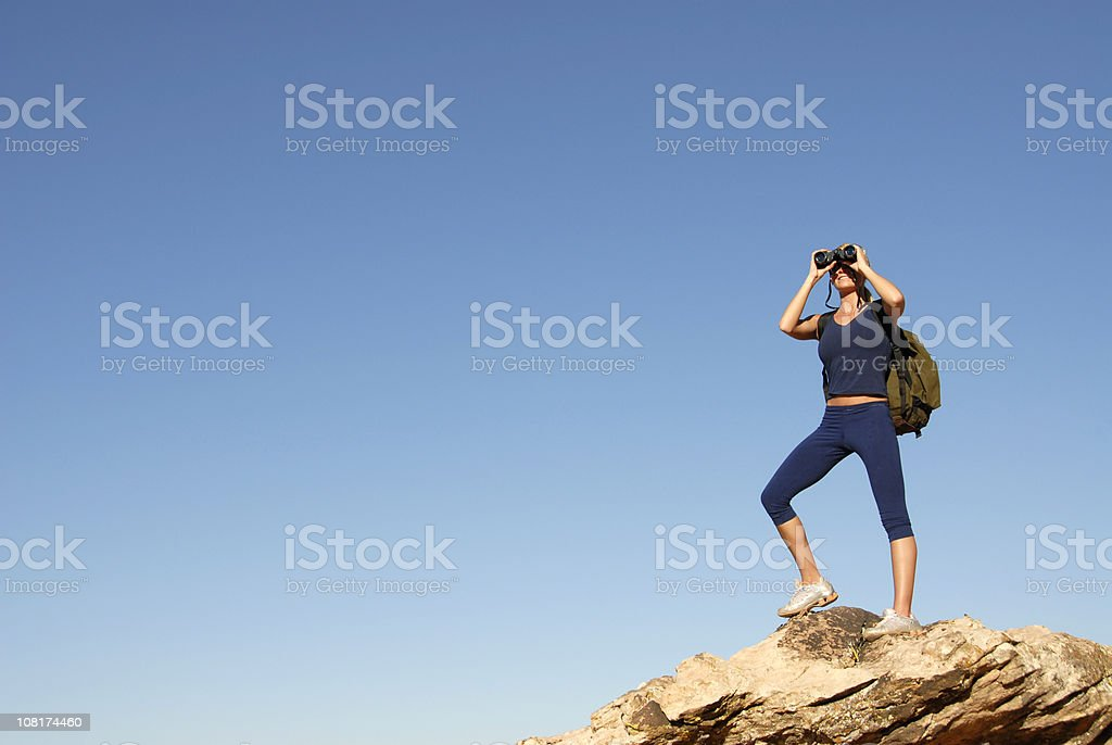 Woman Hiking and Looking Through Binoculars royalty-free stock photo