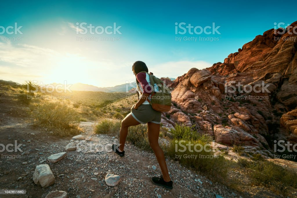 woman hiking at Red Rock Canyon during sunset with backpack - Royalty-free Active Lifestyle Stock Photo