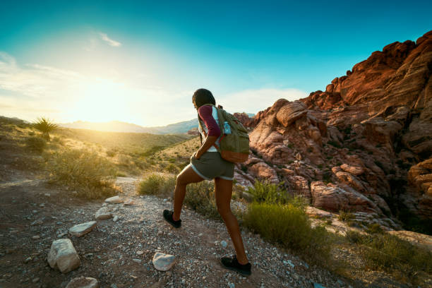 woman hiking at Red Rock Canyon during sunset with backpack woman hiking at Red Rock Canyon during sunset with backpack shot with lens flare hiking stock pictures, royalty-free photos & images