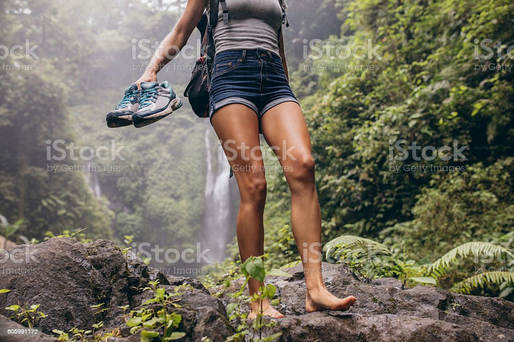 Woman hiking barefoot on forest trail стоковое фото