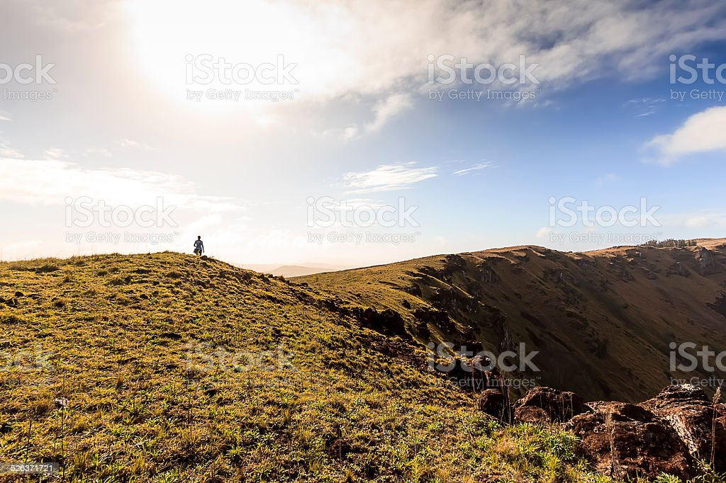 Woman Hiking Beside Volcano Crater in Easter Island stock photo