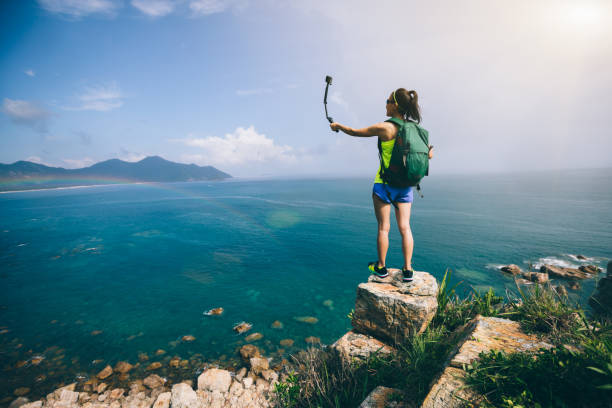 Woman Hiking In Seaside Taking A Selfie stock photo