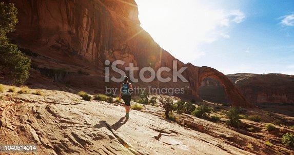 Woman hiking in the Colorado plateau: Corona arch near Moab