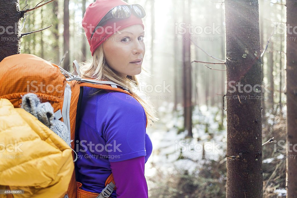 Woman hiking in winter forest sunlight royalty-free stock photo