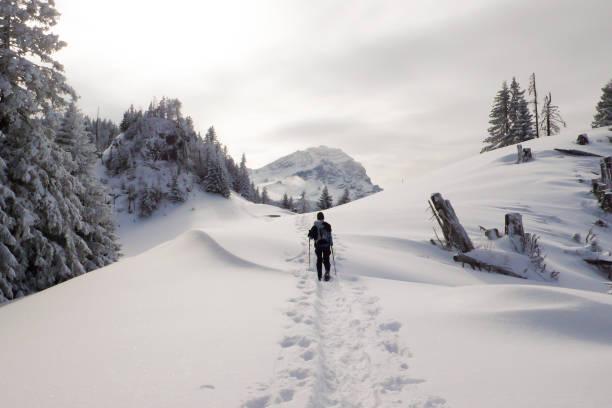 Frau an einem schönen Tag in den Winter Berglandschaft der Alpen der Schweiz mit Schneeschuhen wandern – Foto