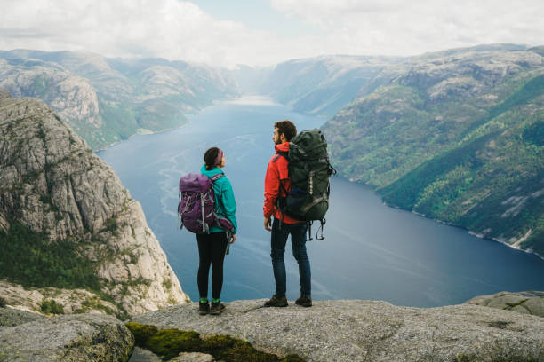 Woman hiking near Preikstolen and looking at Lysefjorden stock photo