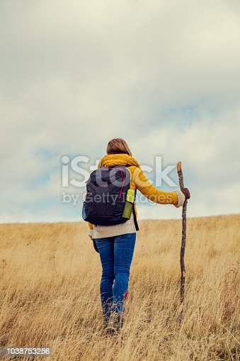 Woman hiking on a empty mountain meadow.