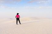 A woman hiking on  on beautiful sand desert, White Sands National Monument, New Mexico;