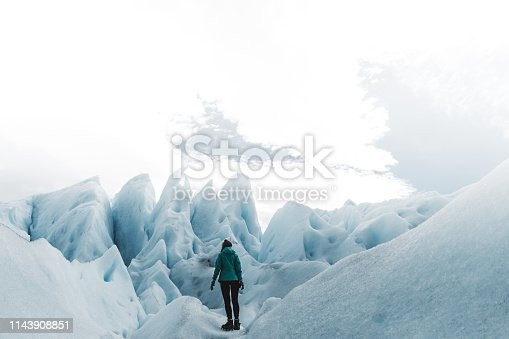 Silhouette of woman in green jacket enjoying her hiking trip on beautiful turquoise colored glacier Perito Moreno in Argentinian Patagonia