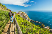Woman hiking on the path in vineyard near Manarola village. Cinque Terre. Liguria, Italy.