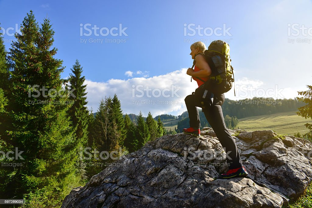 Woman hiking on the rock with backpack photo libre de droits