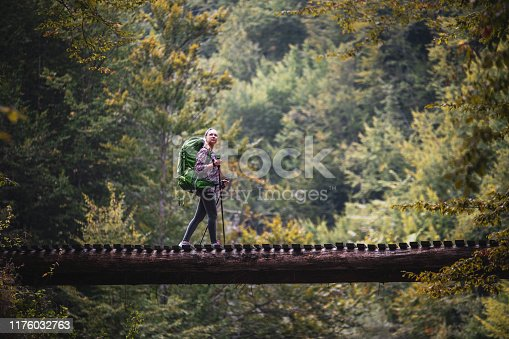 Woman hiking in nature, she walking on footbridge over beautiful river in mountain.