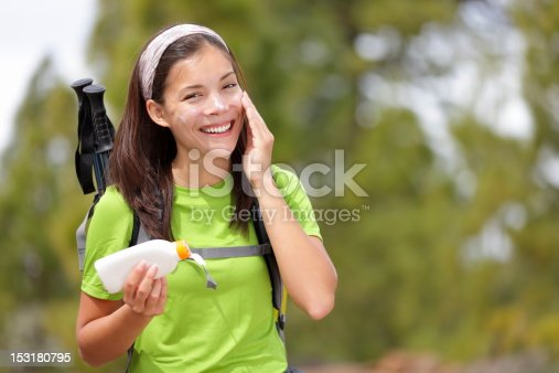 istock woman hiking putting sunscreen 153180795