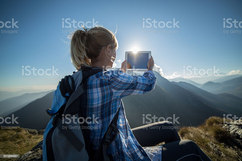 Woman hiking taking picture with digital tablet stock photo