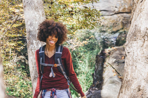 woman hiking through the forest stock photo