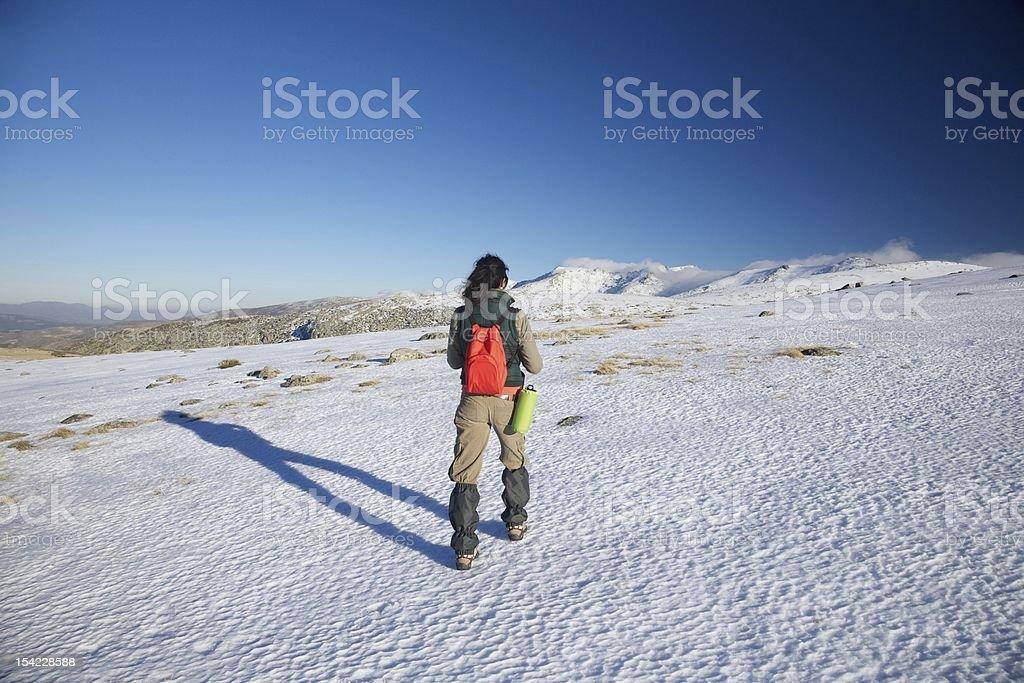woman hiking to snow mountains stock photo
