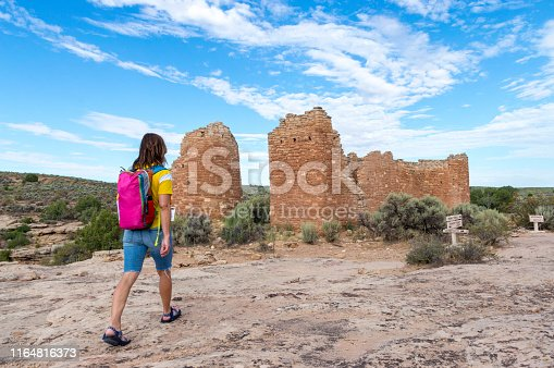This is a woman hiking toward some of the Native American (Anasazi) ruins found at Hovenweep National Monument.  This shot was taken from the top of the Mesa that surrounds the Square Tower Group.  Featured in this shot is a structure called the Hovenweep Castle