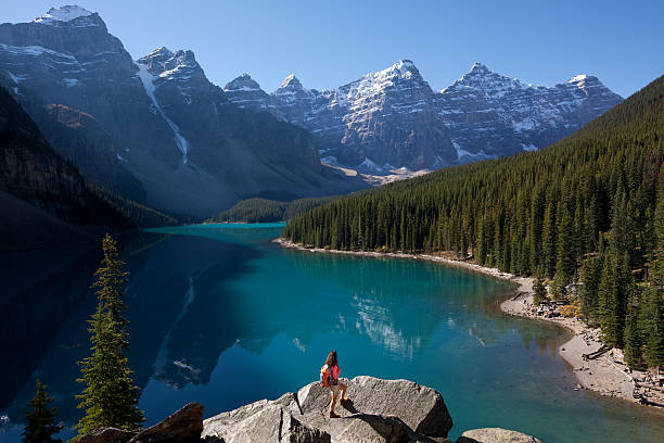 Woman Hiking With Backpack at Moraine Lake, Alberta, Canada Female backpacker standing on boulder admiring majestic view of Moraine Lake and Canadian Rockies. canadian rockies stock pictures, royalty-free photos & images