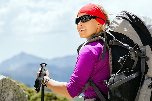 Woman hiking with backpack in mountains stock photo