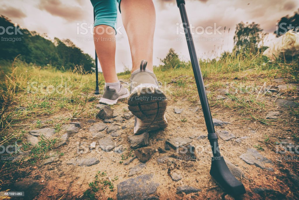 Woman hiking with sticks stock photo