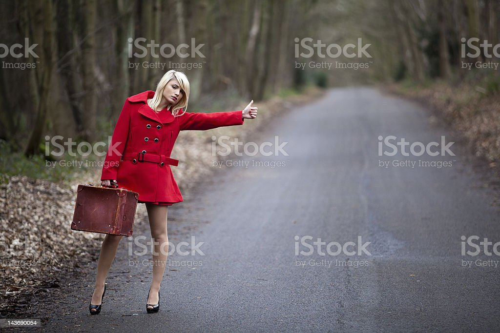 Woman hitch hiking in woods stock photo