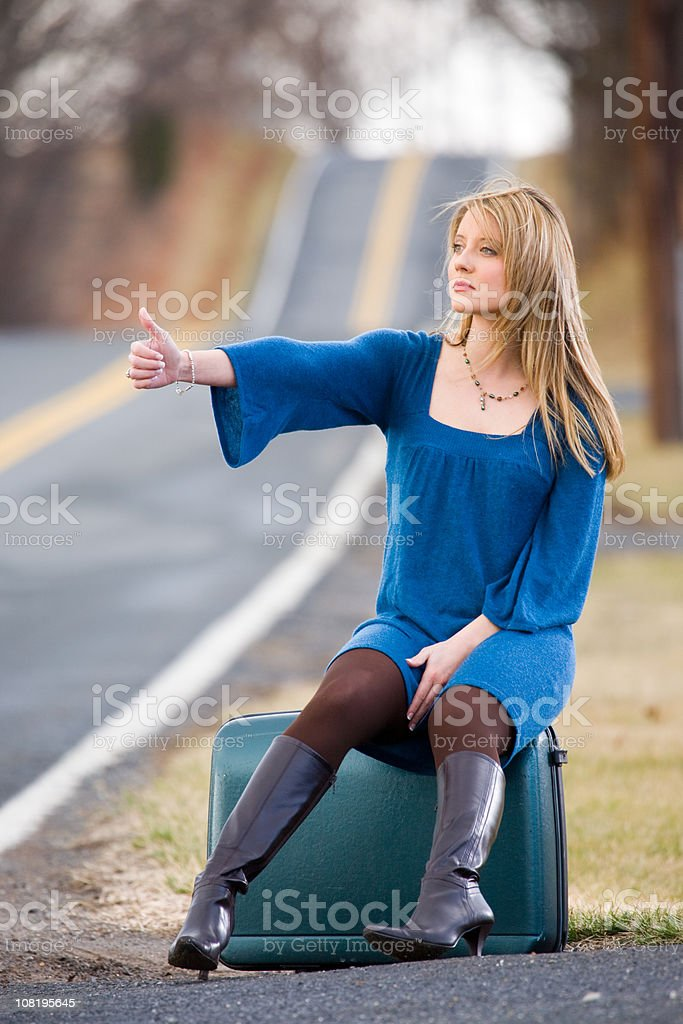 Woman hitchhiking on side of road royalty-free stock photo
