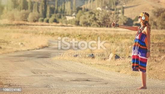 Woman hitchhiking on the road while listening to music with headphones