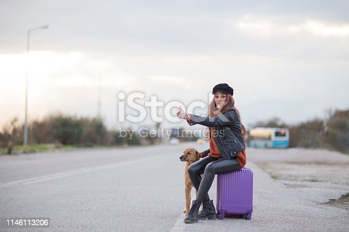 woman hitchhiking with dog