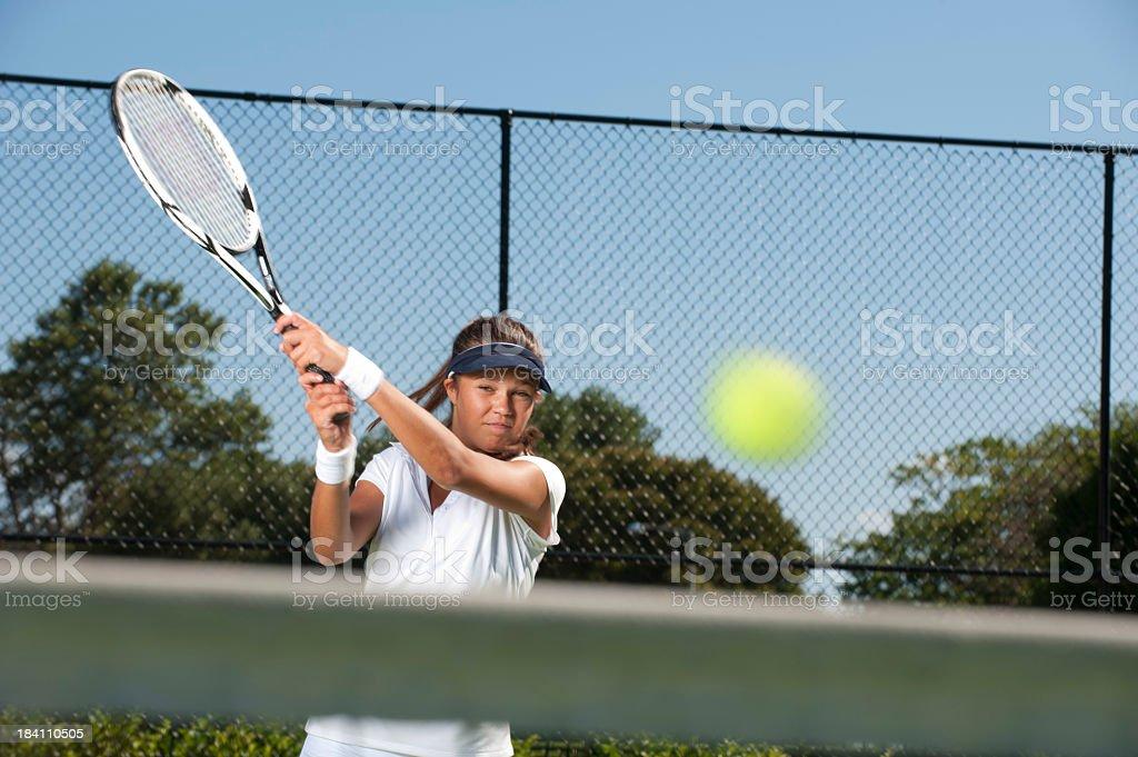 Woman hitting a tennis ball royalty-free stock photo