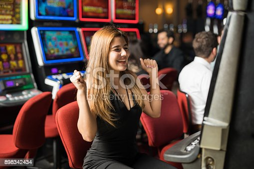 Pretty Caucasian young woman celebrating she just won some money in a slot machine