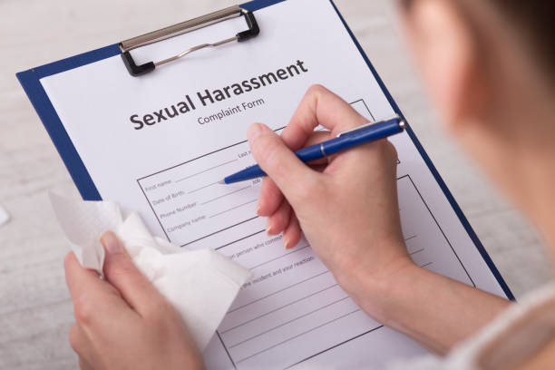 woman hold handkerchief  and  filling Sexual Harassment Complaint Form stock photo