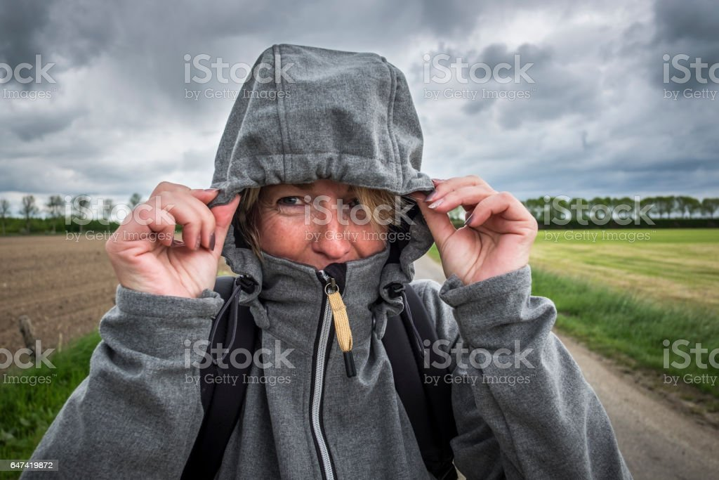 woman hold her hood of the jacket with both hands stock photo