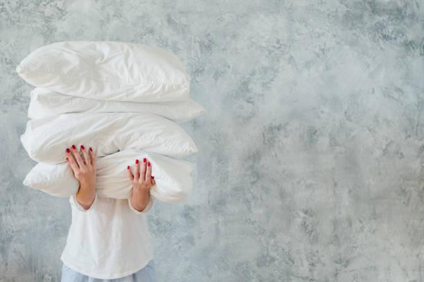 almohadas de pila blanca mujer mantener ropa de cama para dormir - foto de stock