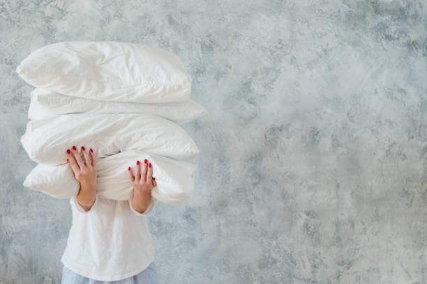 woman hold pile white pillows bedding sleeping - подушка стоковые фото и изображения