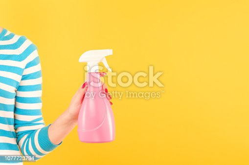 istock woman hold pink spray bottle yellow home cleaning 1077723794