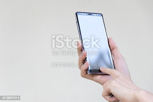 istock Woman hold Samsung Galaxy Note 8 on brown concrete wall background, This mobile phone use android OS. 915697014
