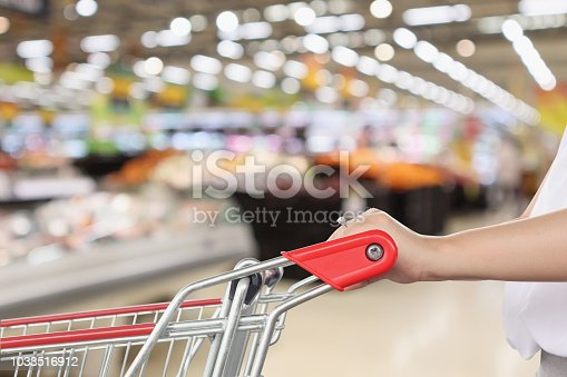 922721264 istock photo woman hold shopping cart with blur supermarket fresh product shelves background 1033516912