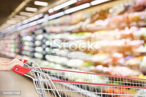 922721264 istock photo woman hold shopping cart with blur supermarket fresh product shelves background 1043927038