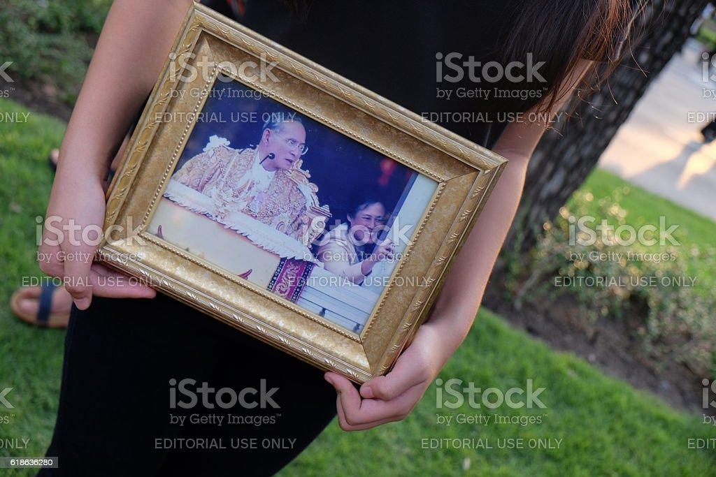 woman hold the portrait of King Bhumibol Adulyadej stock photo