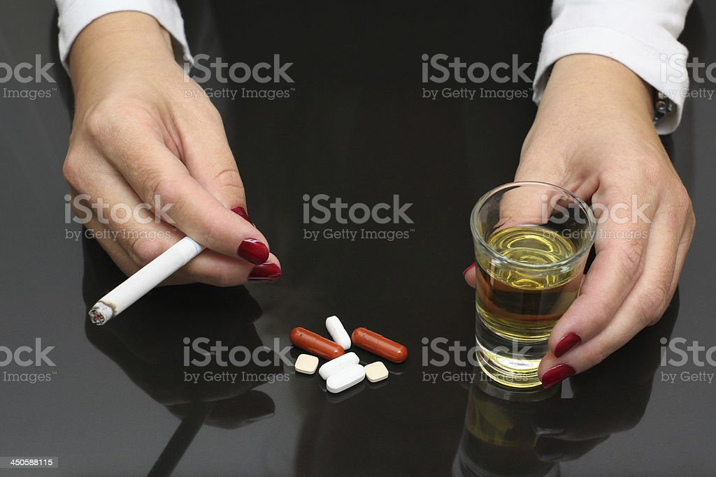 woman hold whiskey and cigarette in hands, drugs on table stock photo