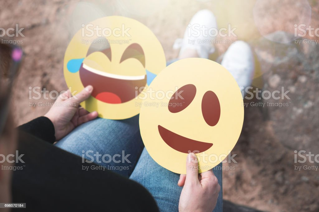 Woman holding 2 cardboard emoticons in hand. Happy laughing and smiling faces. Two modern communication and   expression icons printed on paper. Happiness, joy and expressing feelings concept. – zdjęcie