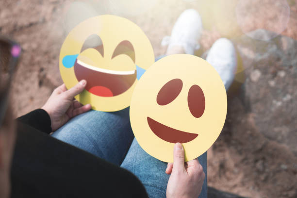 woman holding 2 cardboard emoticons in hand. happy laughing and smiling faces. two modern communication and   expression icons printed on paper. happiness, joy and expressing feelings concept. - emotion stock pictures, royalty-free photos & images