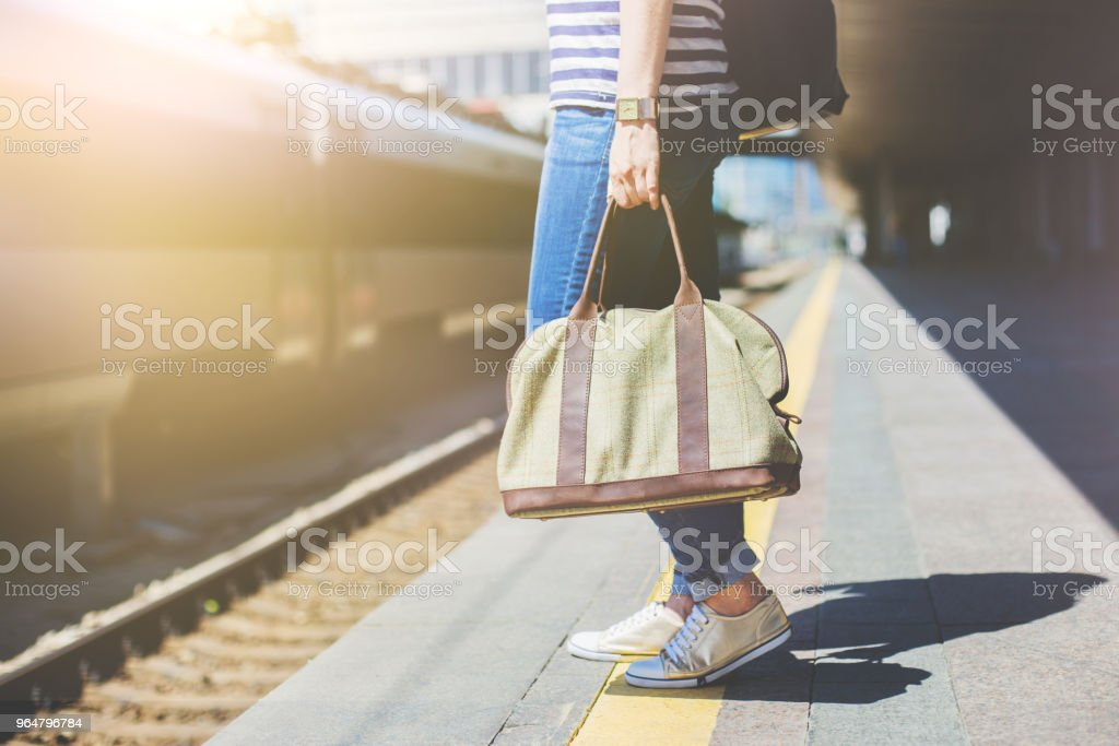 Woman holding a bag at a train station. royalty-free stock photo