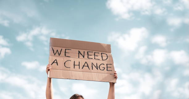 Woman holding a banner of 'We Need A Change'. Problem in ecology, environment, global warming, industrial influence, climate emergency stock photo