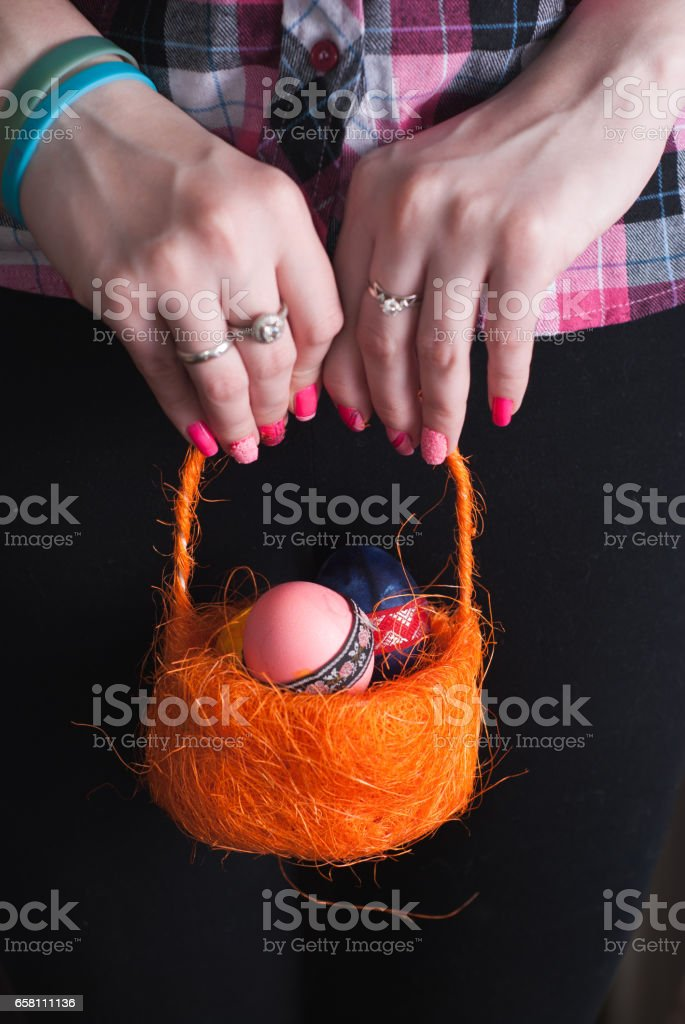 Woman holding a basket of colored eggs , royalty-free stock photo