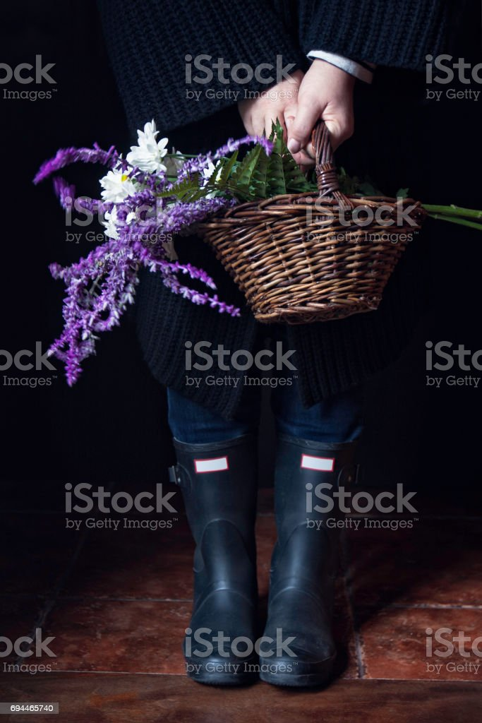 Woman holding a basket with flowers stock photo